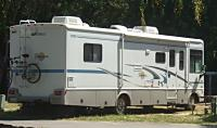 A large RV with an awning and a bike rack